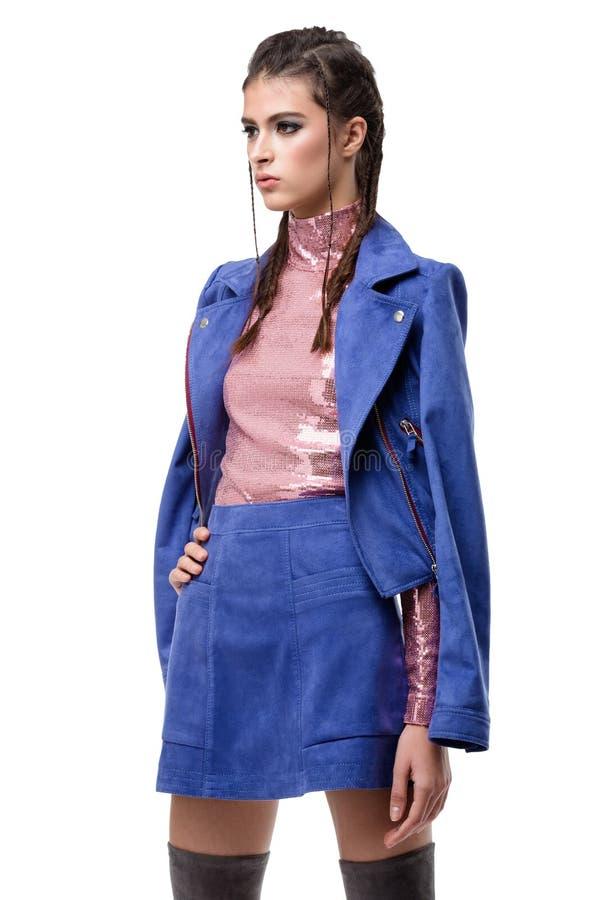 蓝色绒面革裙子和夹克的宇宙夫人和与衣服饰物之小金属片的桃红色上面在被隔绝的白色背景 免版税图库摄影