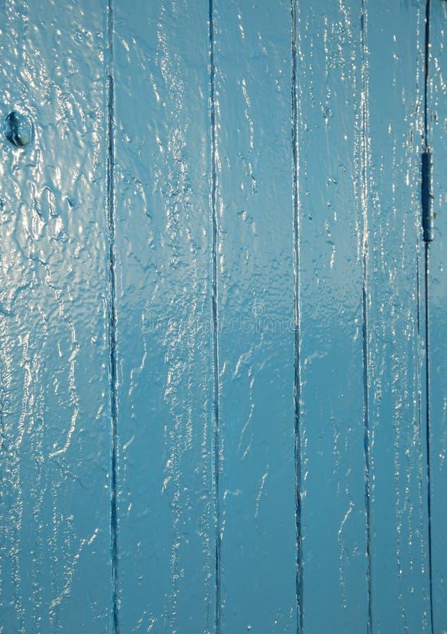 蓝色绘了门显示表面缺点和反射的纹理背景 免版税库存图片