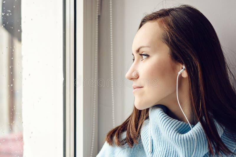 蓝色羊毛毛线衣的年轻深色的妇女听到在耳机的音乐的通过在窗台的一个智能手机在的屋子里 库存图片