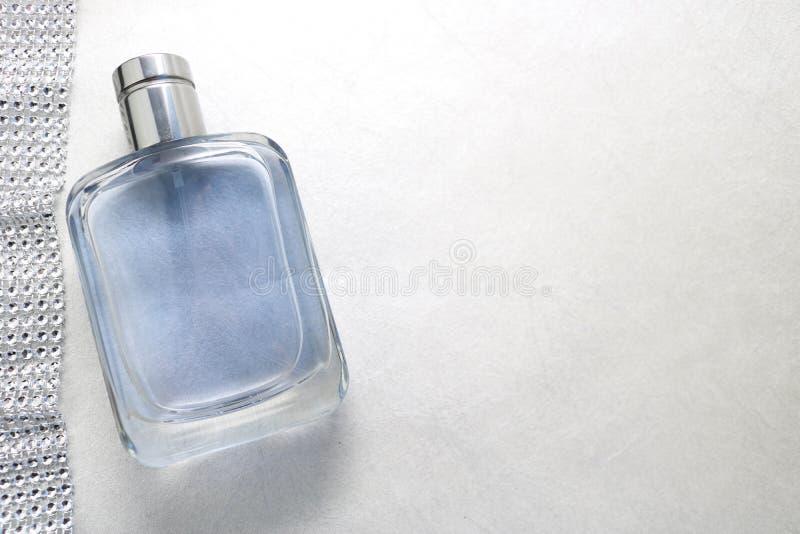 蓝色美丽的玻璃透明时兴的迷人的瓶科隆香水、闪耀的假钻石的金刚石香水和丝带  免版税库存图片