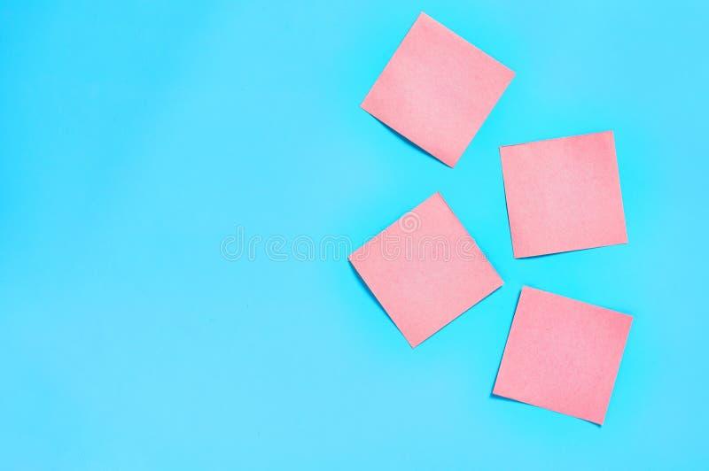 蓝色背景上的四个粉红色方形空白纸贴纸 库存照片