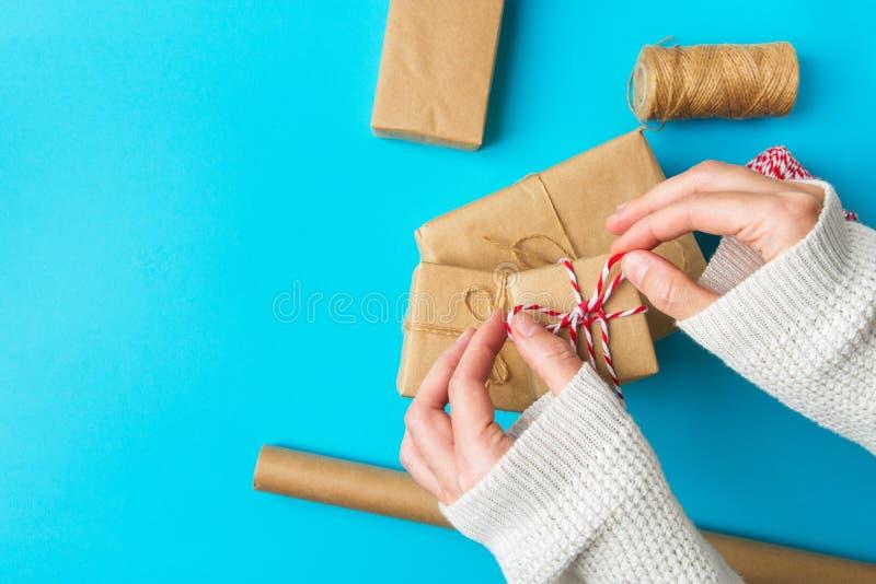 蓝色背景上,年轻白人女性手包圣诞新年礼盒上的棕色卡夫丝带 库存图片