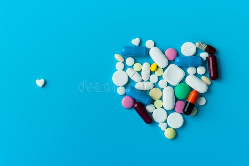 蓝色背景下的药丸、片剂和胶囊。蓝色背景下的瓶中药物、补充剂和药物 图库摄影