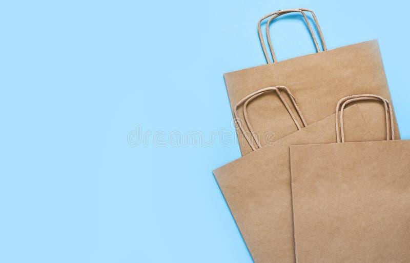 蓝色背景下购物的手工纸袋 平的 礼品袋 库存照片