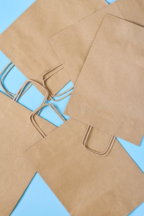 蓝色背景下购物的手工纸袋 平的 礼品袋 免版税图库摄影