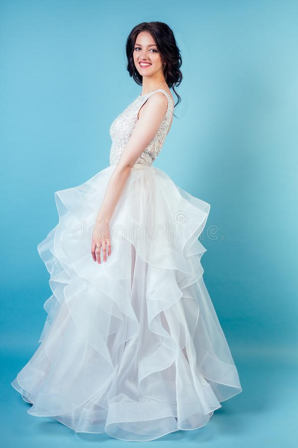 蓝色背景下,在工作室里,化妆成长而别致的白色婚纱的年轻漂亮女新娘 概念 免版税库存照片