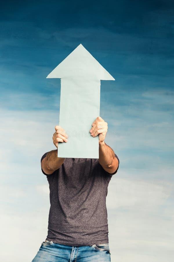 蓝色背景中一个身穿灰色T恤的男子,手里拿着一支箭,遮住脸 箭头指向上, 库存图片