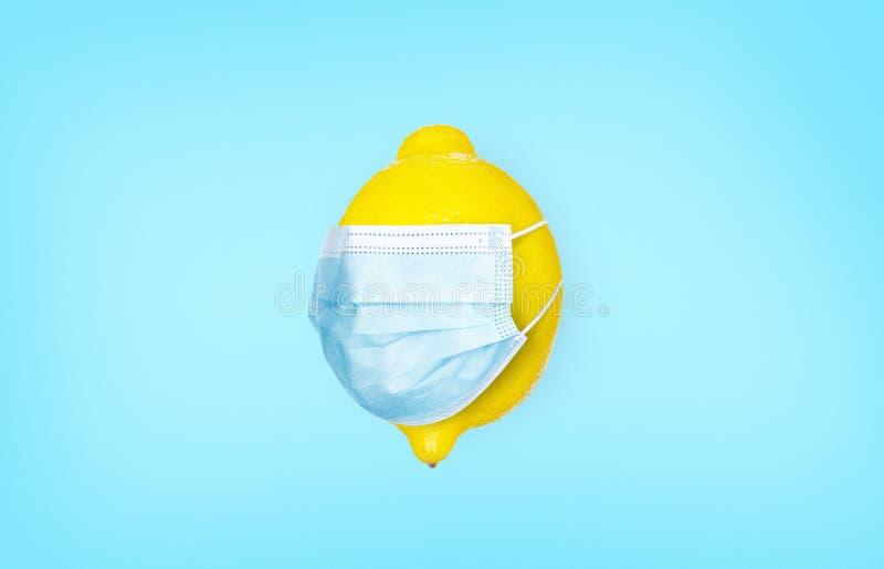 蓝色背景中带医用口罩的柠檬 感冒维生素 冠状病毒保护概念 感染与预防 图库摄影