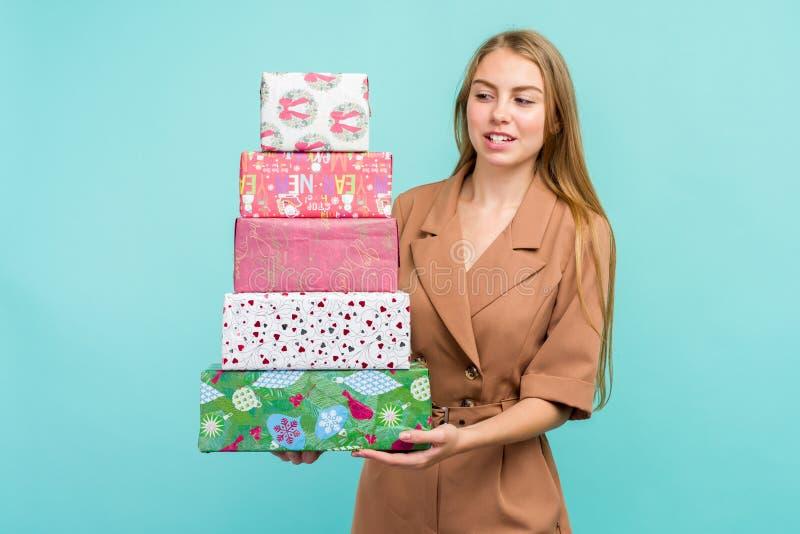 蓝色背景中拿着礼盒的快乐漂亮的年轻女子 免版税库存图片