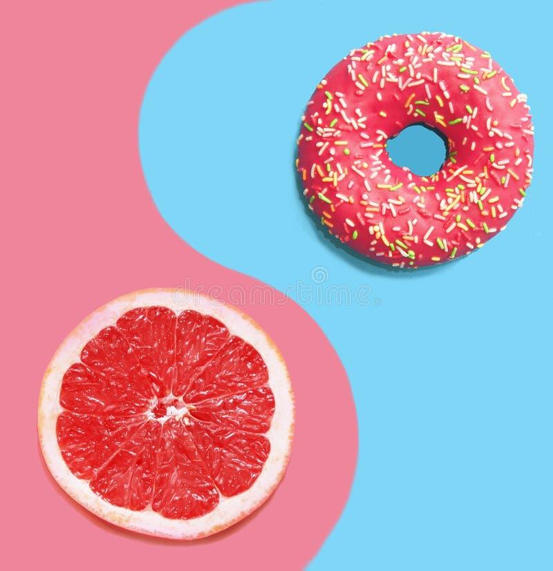 蓝色背景中的甜甜圈和粉色葡萄柚 库存照片
