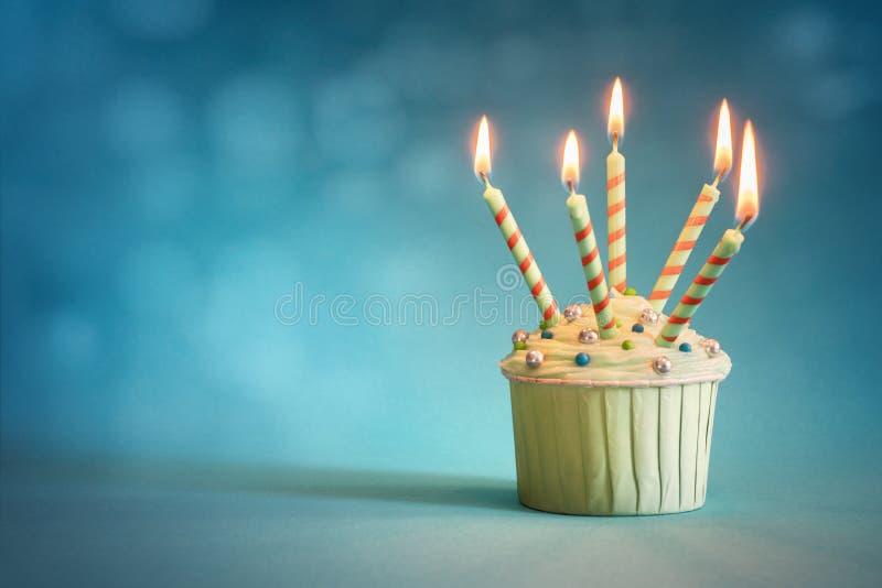 蓝色背景中的生日纸杯蛋糕 库存图片