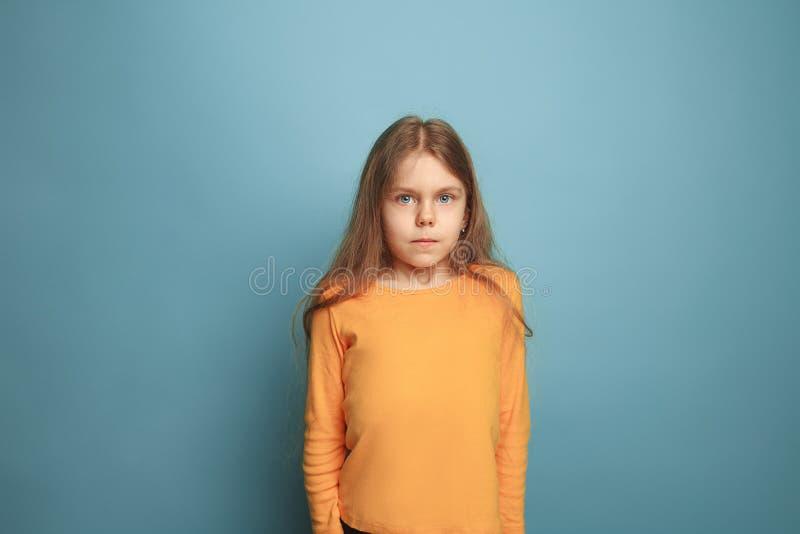 蓝色背景的严肃的青少年的女孩 表情和人情感概念 免版税库存图片