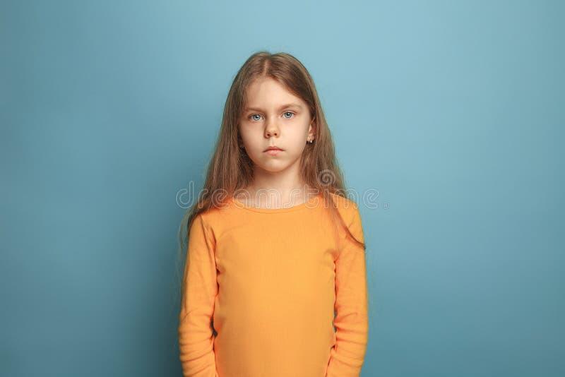 蓝色背景的严肃的青少年的女孩 表情和人情感概念 免版税库存照片