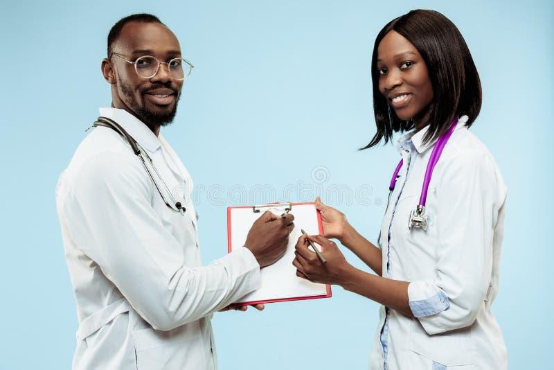 女性被�yf�x�~��_蓝色背景的女性和男性f愉快的美国黑人的医生.