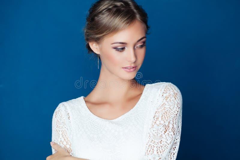蓝色背景的年轻友好的妇女 免版税库存图片