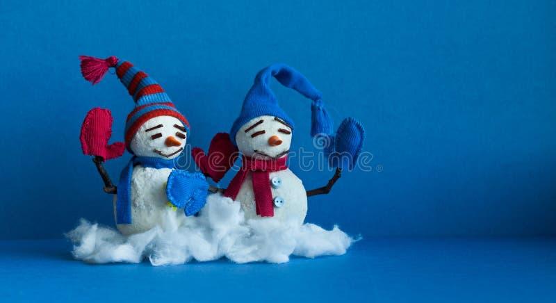 蓝色背景的愉快的雪人 与围巾手套和滑稽的帽子的冬天传统雪人字符 Xmas新年 免版税库存图片