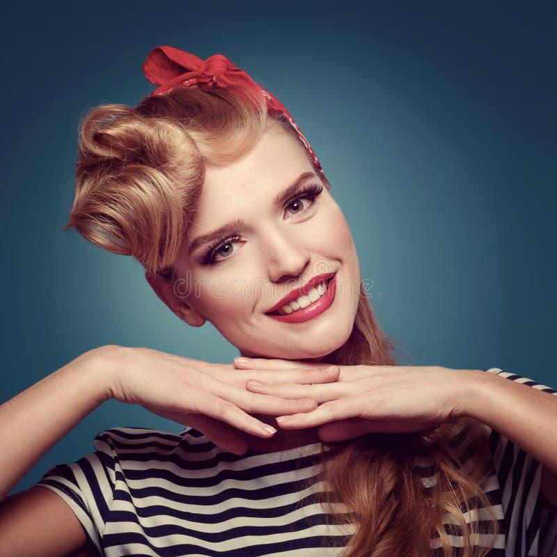 蓝色背景的秀丽微笑的画报女孩 免版税图库摄影