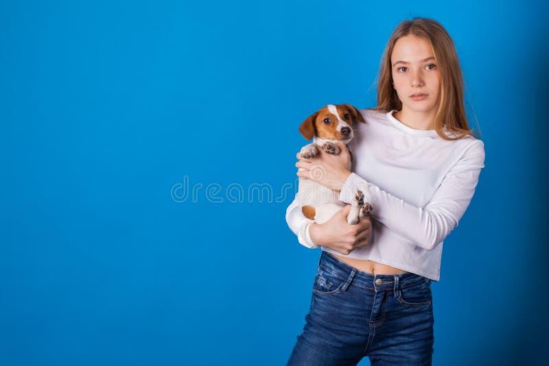 蓝色背景的美丽的时髦的青少年的女孩 免版税库存图片