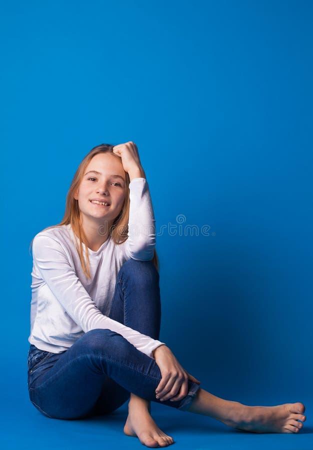 蓝色背景的美丽的时髦的青少年的女孩 免版税库存照片