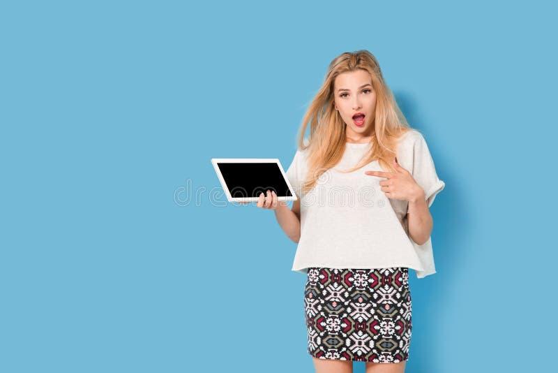 蓝色背景的年轻美丽的妇女 免版税图库摄影