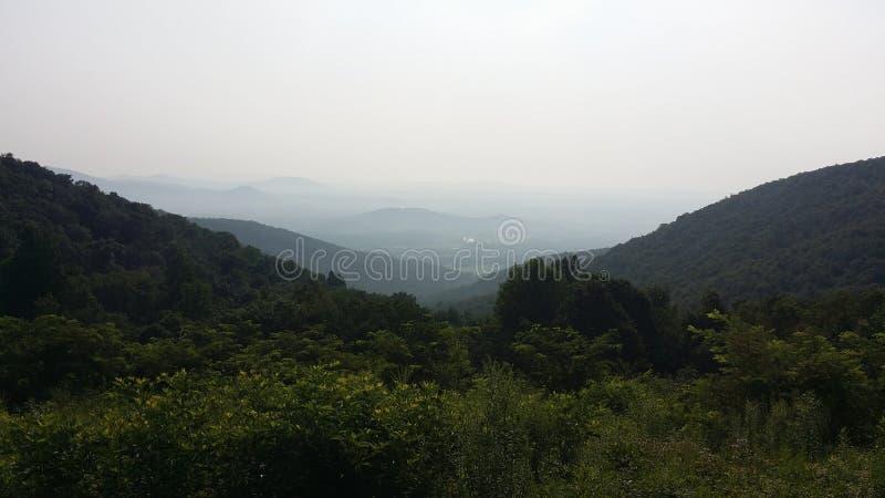 蓝色背脊山的小山沿地平线的驾驶 免版税库存图片