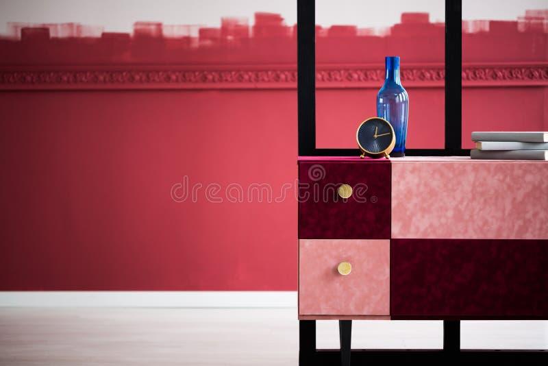 蓝色花瓶、书和金黄公鸡在粉红彩笔和伯根地洗脸台 库存图片