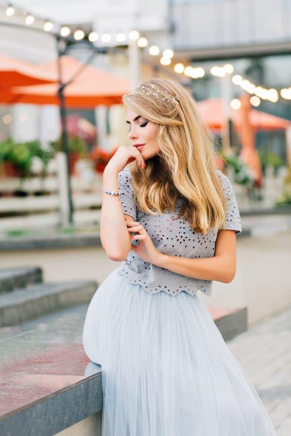 蓝色薄纱裙子的俏丽的白肤金发的女孩坐大阳台背景 作梦与闭合的眼睛的她 图库摄影