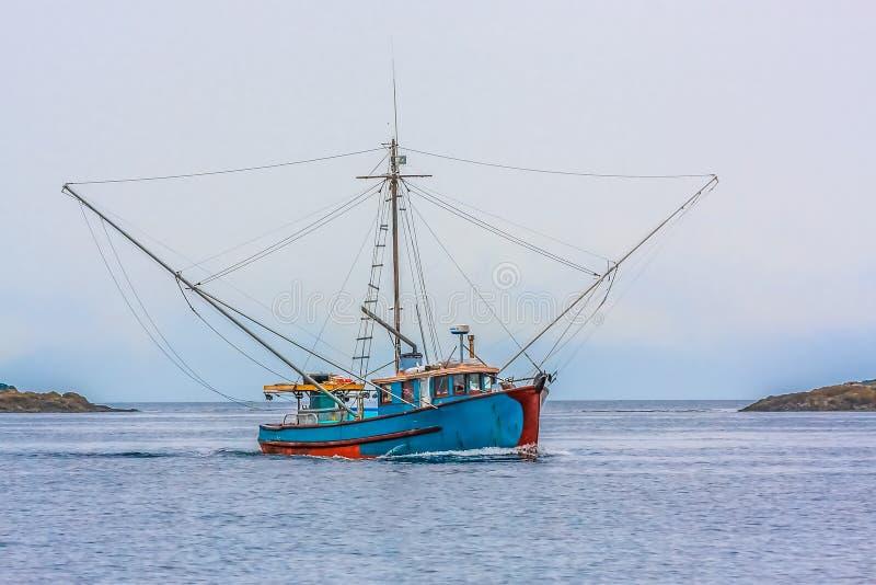 蓝色虾小船在灰色天 免版税库存图片