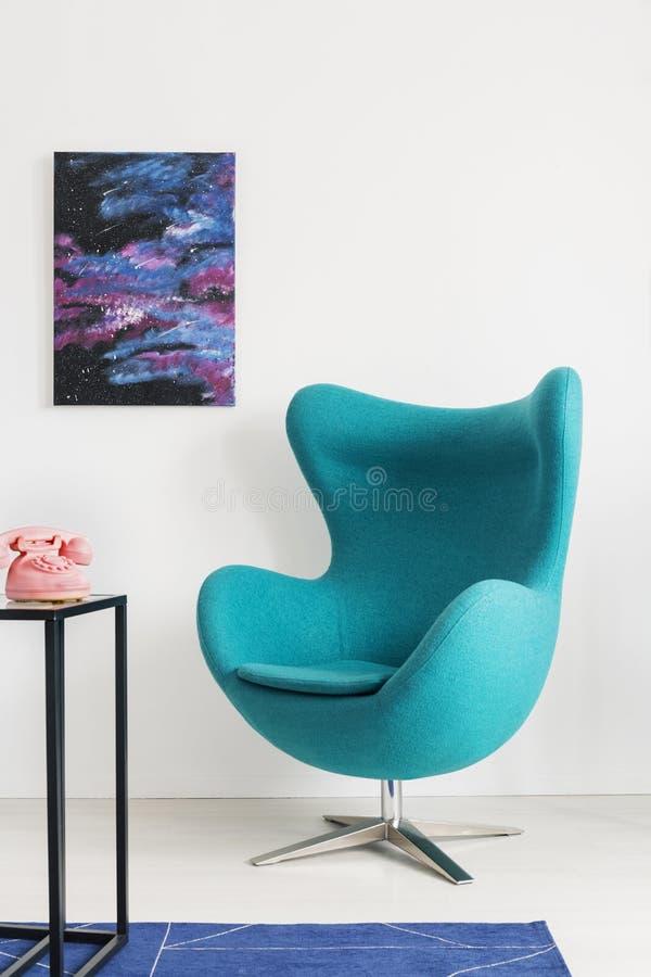 蓝色蛋椅子垂直的看法在金属架子旁边的与桃红色电话,在墙壁上的波斯菊图表,与拷贝空间的真正的照片 免版税库存照片