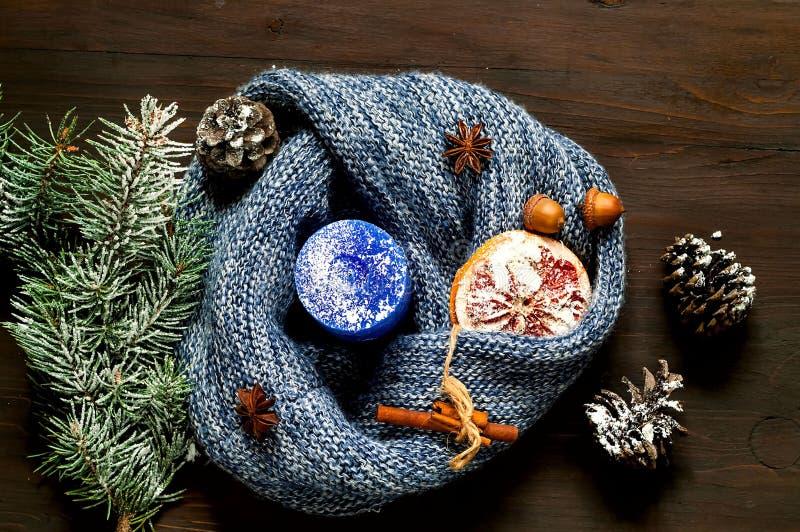 蓝色蜡烛和被编织的围巾在木背景 舒适圣诞节装饰的概念 Hugge样式 特写镜头 库存照片