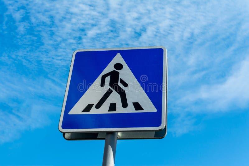 蓝色行人交叉路标志关闭反对多云天空 免版税库存照片