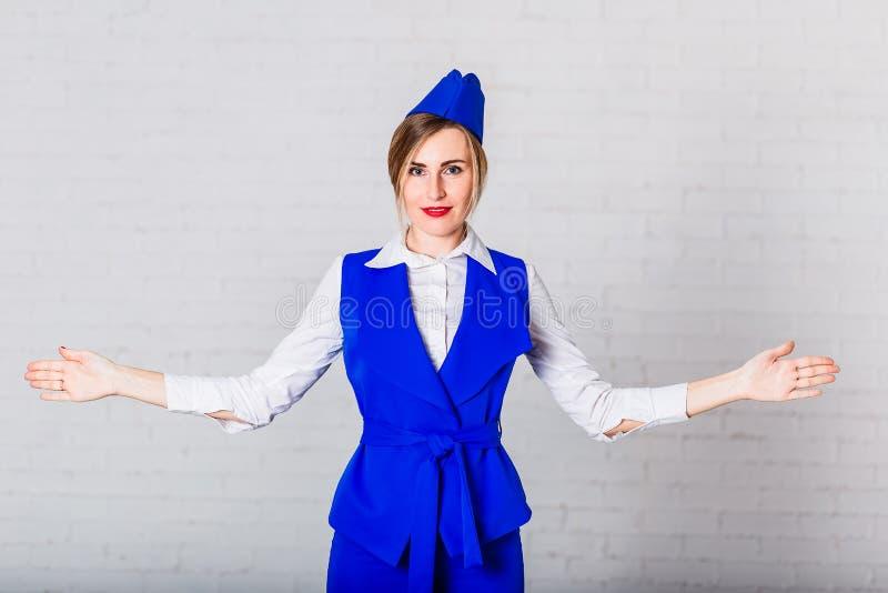 蓝色衣服的空中小姐举他的手对边 免版税库存照片