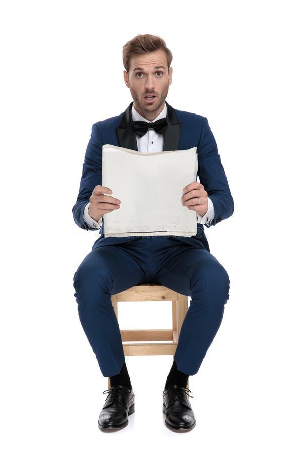 蓝色衣服读书报纸的安装的震惊人 免版税图库摄影