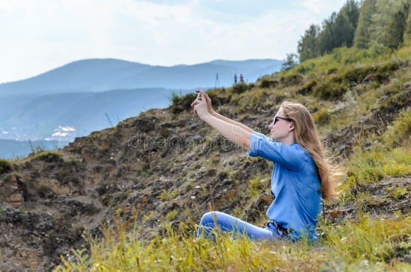 蓝色衣裳的,做selfie的佩带的太阳镜女孩在夏天户外 库存图片