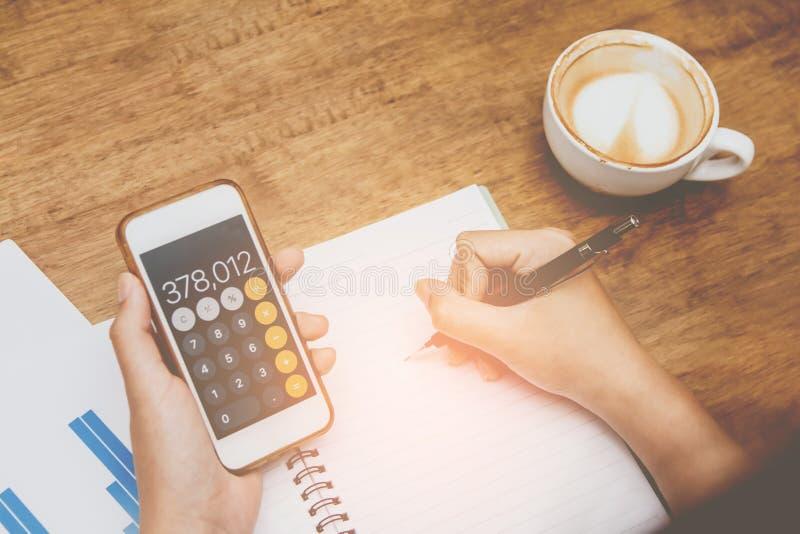 蓝色衬衣候宰栏工作的亚裔年轻女人,在手机税主角计算对清盘 免版税库存照片