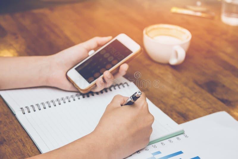 蓝色衬衣候宰栏工作的年轻女人,在手机税主角计算对清盘 免版税库存照片