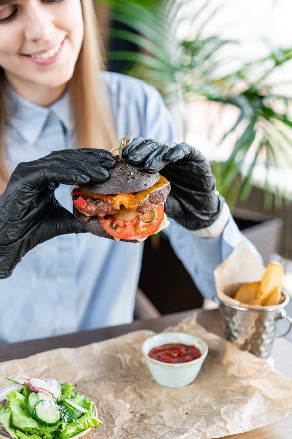 蓝色衬衣和黑手套的年轻女人吃与牛肉剁的可口水多的汉堡包 在咖啡馆的汉堡与 免版税库存照片