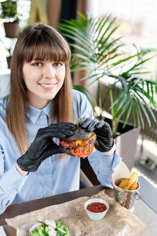 蓝色衬衣和黑手套的年轻女人吃与牛肉剁的可口水多的汉堡包 在咖啡馆的汉堡与 图库摄影