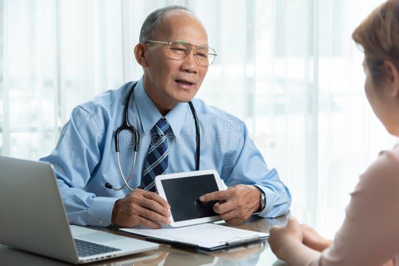 蓝色衬衣的亚裔资深男性医生谈话与他的患者 免版税库存图片