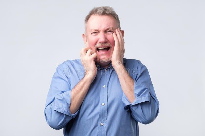 蓝色衬衣的哭泣疯狂的老人知道坏消息 免版税库存图片
