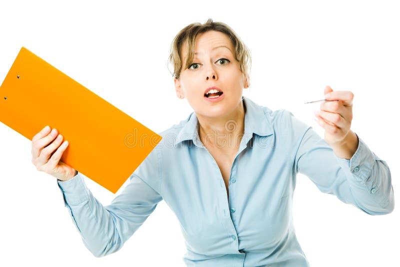 蓝色衬衣的女商人拿着橙色笔记情感地表现-呼喊的不安定的上司 免版税库存照片