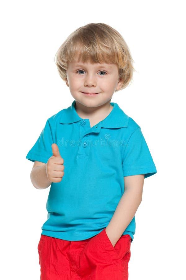 蓝色衬衣的小白肤金发的男孩举行他的赞许 免版税库存照片