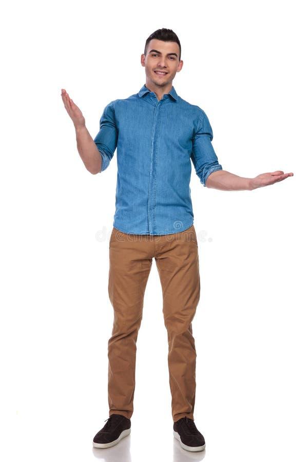 蓝色衬衣的帅哥做一个欢迎姿态 库存图片