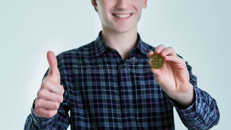 蓝色衬衣的年轻人拿着bitcoin并且显示被举的拇指 背景查出的白色 bitcoin的概念  图库摄影