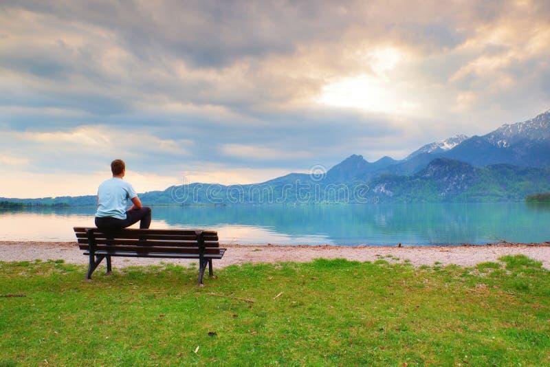 蓝色衬衣的疲乏的成人人坐老长木凳在山湖海岸 免版税库存照片