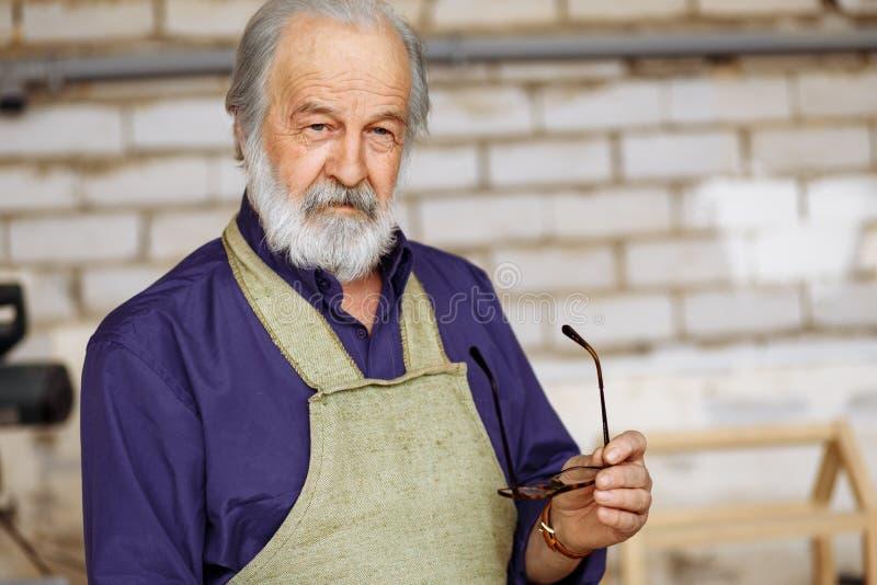 蓝色衬衣的老灰发的摆在照相机的木匠和围裙,当工作时 库存照片
