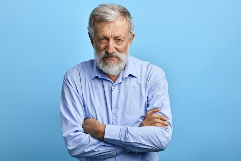蓝色衬衣的英俊的老人有怀疑表示的 库存图片