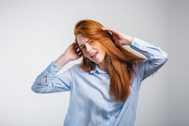 蓝色衬衣跳舞的红发关于某事的妇女或欣喜 免版税库存照片