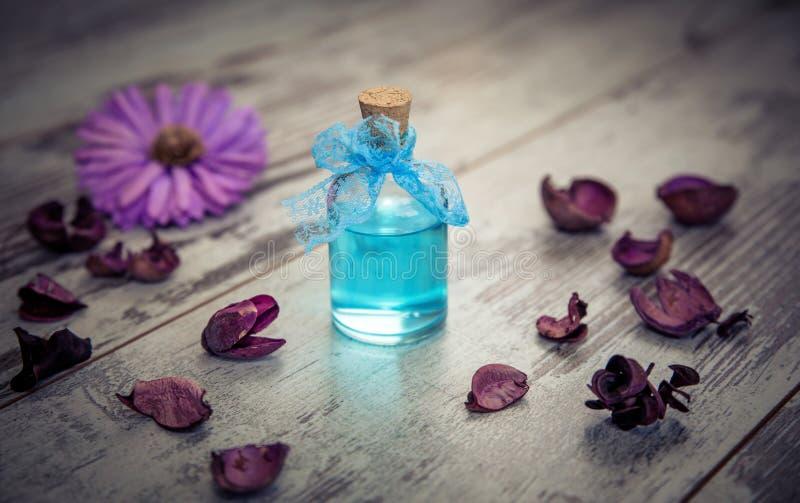 蓝色被定调子的科隆香水和干燥花 免版税库存照片