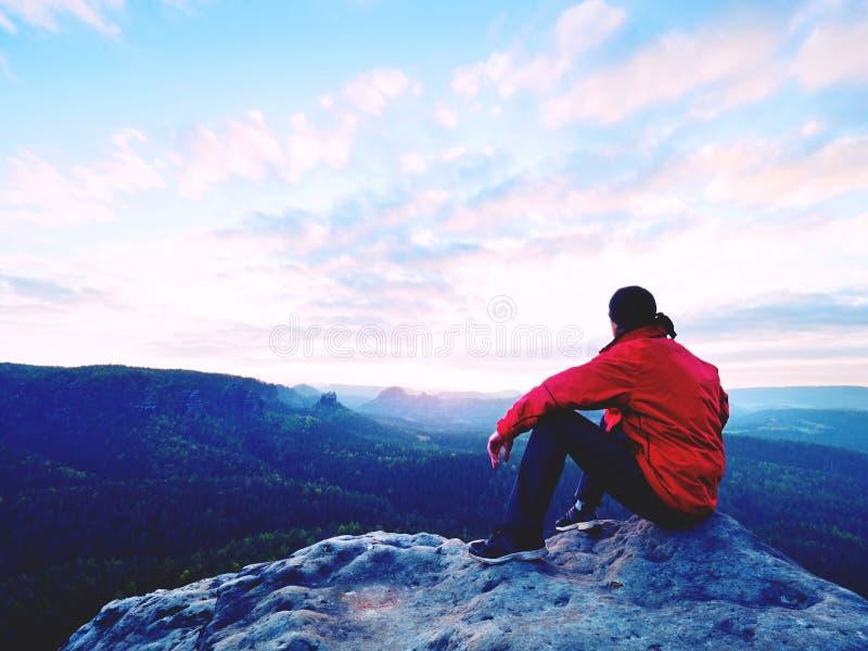 蓝色被过滤的照片 红色夹克的人认为在岩石峭壁的 忧郁晚上本质上 库存图片